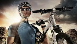 Sport. Cyclist carry a bike on dramatic sky.